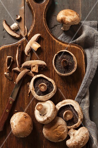 Fresh mushrooms, partially sliced, with an old-fashioned knife on a chopping board