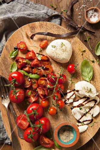 Mixed tomatoes with mozzarella and basil, black pepper, thyme and both balsamic sauce on a wooden board