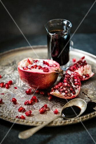 A pomegranate and pomegranate molasses in a glass jug on a silver tray