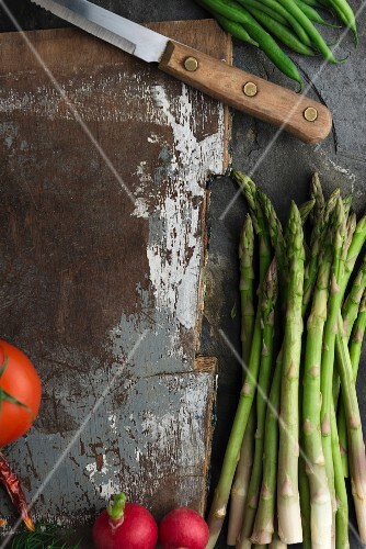 Green asparagus, radishes, tomatoes and beans around an old chopping board with a knife