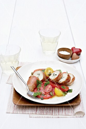 Chicken breast roulade with sage wrapped in Parma ham on a tomato salad