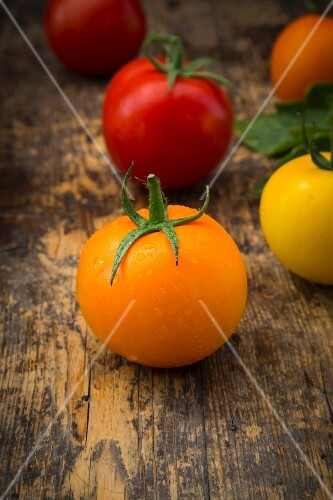 Orange, red and yellow tomatoes on a wooden surface