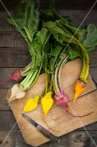 Organic beetroot, golden beets and white beets on a wooden chopping board (seen from above)