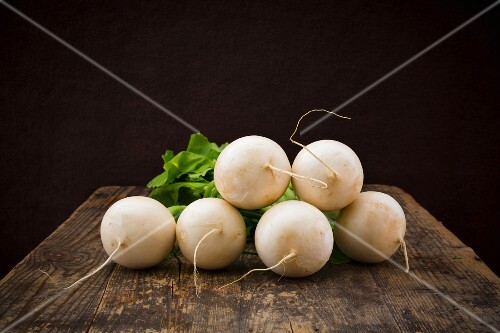 White turnips on a wooden surface against a black background