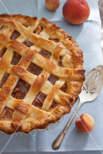 A whole peach pie with a lattice lid