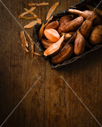Sweet potatoes in a rustic wooden basket and peelings on a wooden table