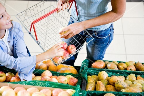 A mother and daughter choosing fruit in a supermarket