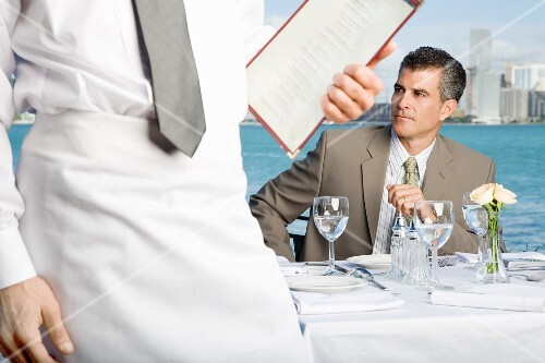 A businessman sitting at a table in a restaurant