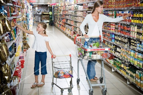 A mother and daughter selecting products in a supermarket
