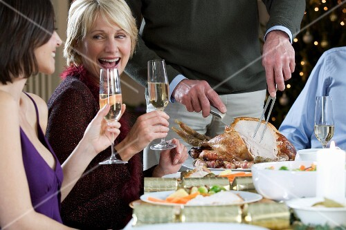 A family eating a festive Christmas dinner with champagne and roast turkey