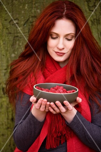 A redhaired woman leaning on a tree holding a bowl of raspberries