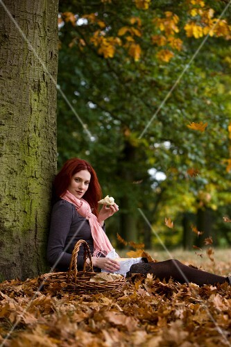 A woman sitting on fallen leaves against a tree having a picnic