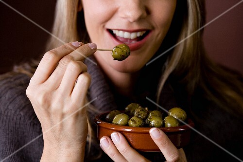A woman eating an olive