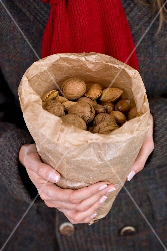 A woman holding a paper bag of assorted nuts
