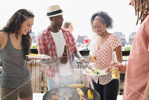 A group of multicultural young people having a barbecue on a roof terrace