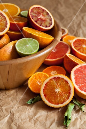 Halved citrus fruit in a wooden bowl and on crumpled paper