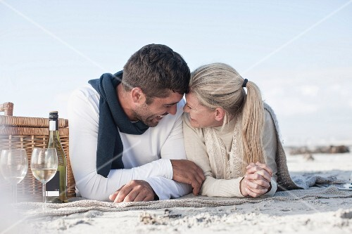 A laughing couple lying on a blanket next to a picnic basket on a sandy beach
