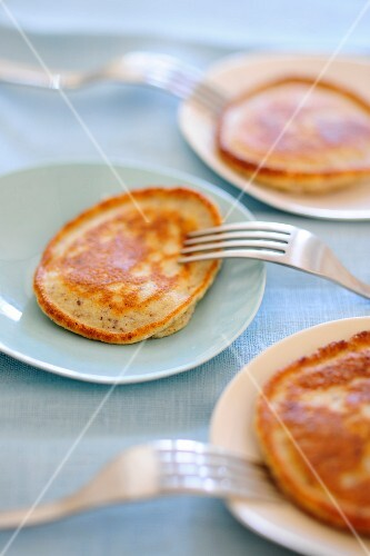 Three plates of pancakes with forks