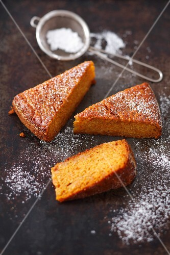Three slices of carrot and sweet potato cake with icing sugar