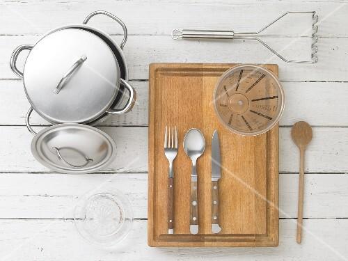 Kitchen utensils: a pot, a citrus juicer, cutlery, a measuring jug and a potato masher