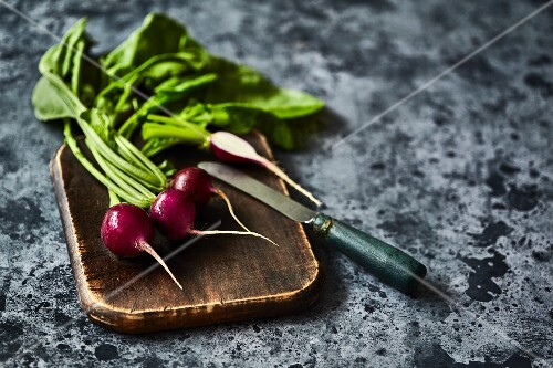 Radishes on wooden board with a knife
