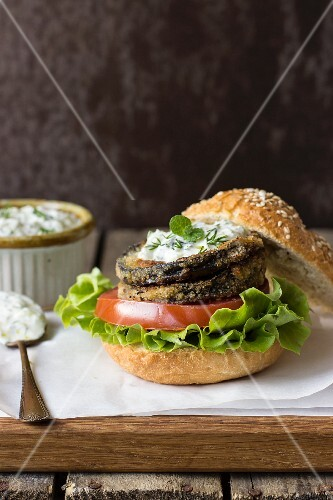 An aubergine burger with fried aubergine slices, Parmesan cheese, walnuts, tomato, lettuce and tzatziki