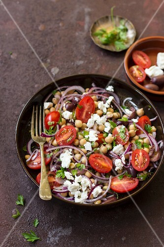 Chickpea salad with cherry tomatoes, feta cheese, onions, parsley and Kalamata olives