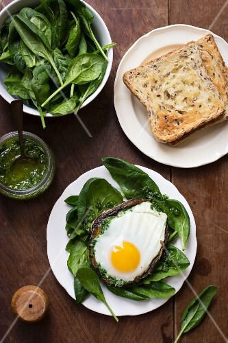 A fried egg on a mushroom on a bed of spinach with a parsley and garlic sauce