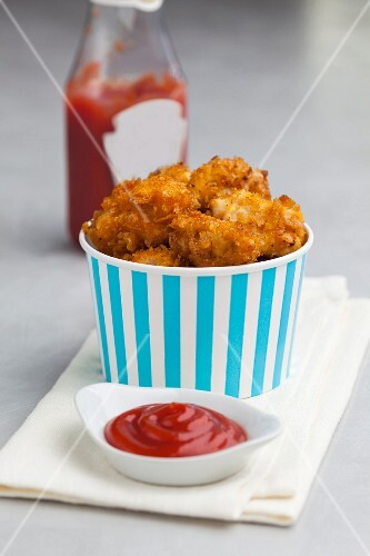 Chicken nuggets with a cornflakes crust served with ketchup