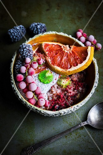 A smoothie bowl with wholemeal oats, coconuts, chia seeds, grapefruit and frozen berries