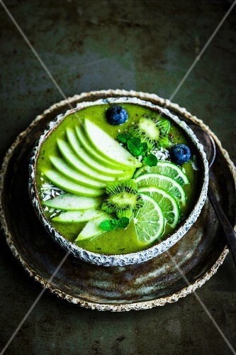 Green smoothie bowl with spinach, banana, apple, coconut water, limes, kiwi flowers and blueberries