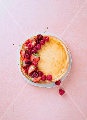 Cheesecake with fresh berries on a coloured surface (seen from above)