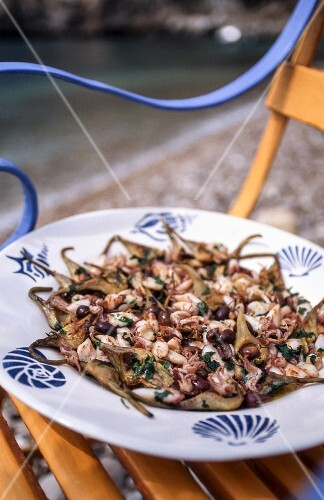 Artichoke salad with squid and olives on a chair outside