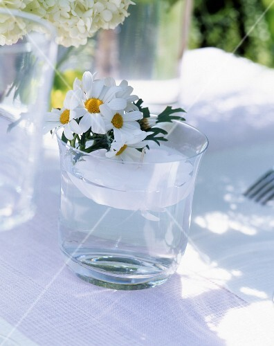 Summer table decorations with floating candles and daisies in a glass of water