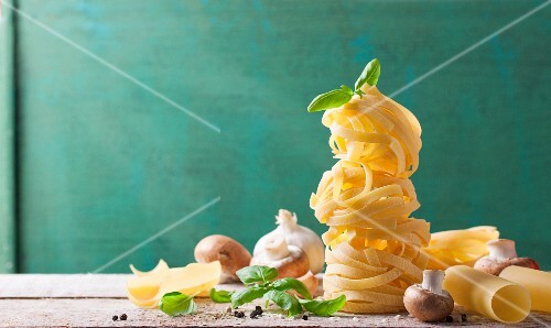 Tagliatelle with mushrooms, basil, garlic and pepper on a wooden board