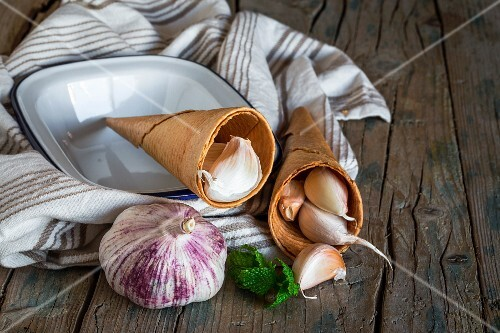 Purple garlic on a tea towel on a rustic wooden table