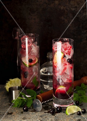 Long drinks with rum, blackcurrant syrup, lime, mint and ice cubes