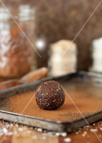 A date energy ball being rolled in cocoa powder