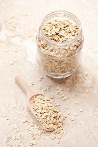 Oats in a jar and on a wooden scoop