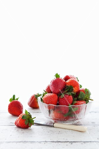 Fresh strawberries in a glass dish and next to the dish