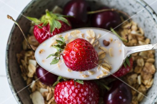 Muesli with strawberries, cherries and oat milk (seen from above, close-up)