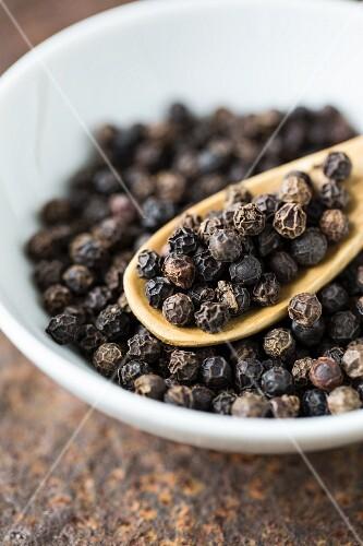 A bowl of black peppercorns (close-up)