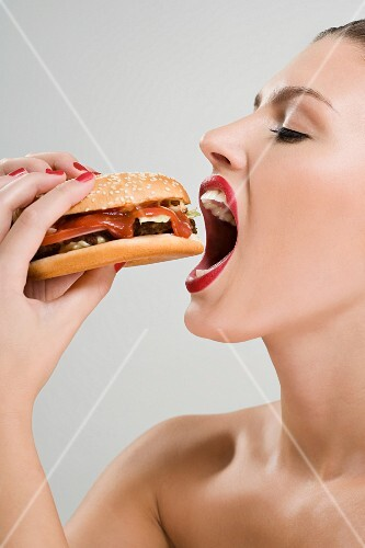 A young woman passionately biting into a hamburger