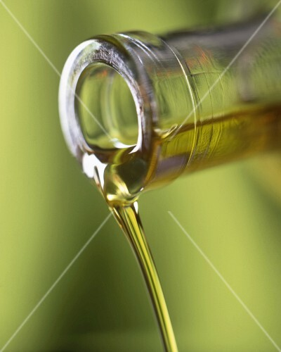 Olive oil flowing from a bottle (close-up)