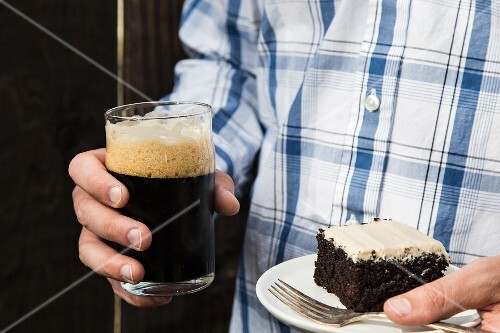 A man holding a slice of chocolate cake and a glass of dark beer