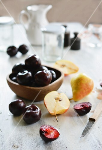 Pears and plums on a white wooden table with empty jam jars and weights in the background