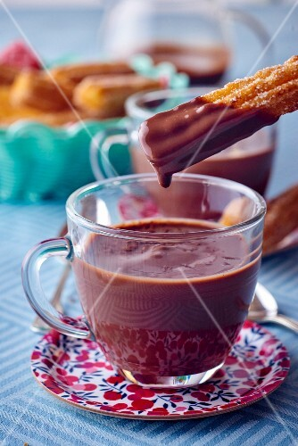 Churros being dipped in hot chocolate
