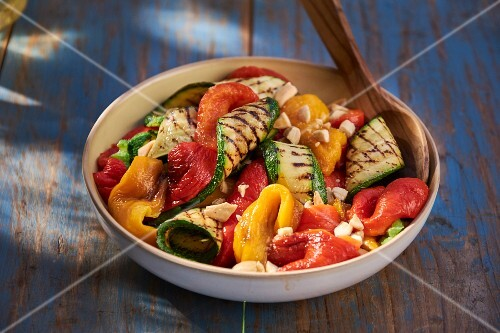 A bowl of grilled vegetables on a table outside