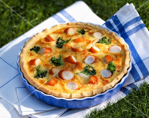 Quiche with surimi and broccoli in a baking dish on the grass