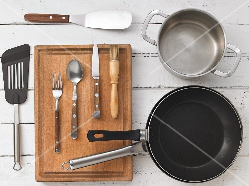 Various kitchen utensils: pans, a pot, a spatula, cutlery and a brush